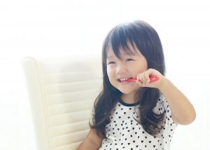 笑顔で歯磨きする子ども